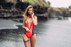 Free Beautiful Sexy Girl With Big Breasts In Red Swimsuit Poses On Black Sand Beach Stock Image - 150888731