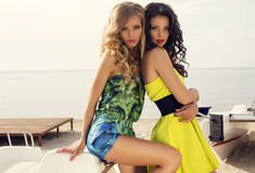 Beautiful girls in dresses posing on beach stock photography