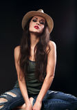 Beautiful sexy glamour female model in cowboy summer hat posing. In fashion top and ripped jeans on dark background Stock Photos