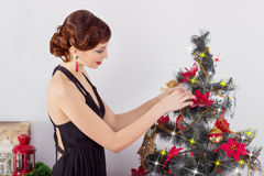 Beautiful happy smiling young woman in evening dress with bright makeup with red lipstick, decorates a Christmas tree Stock Photos