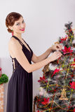Beautiful sexy happy smiling young woman in evening dress with bright makeup with red lipstick, decorates a Christmas tree Royalty Free Stock Photography