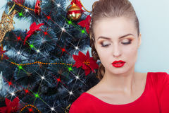 Beautiful happy smiling young woman in evening dress with bright makeup with red lipstick sitting near the Christmas tree Royalty Free Stock Photography