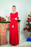 Beautiful sexy happy smiling young woman in evening dress with bright makeup with red lipstick sitting near the Christmas tree Royalty Free Stock Photos