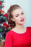Beautiful sexy happy smiling young woman in evening dress with bright makeup with red lipstick sitting near the Christmas tree Stock Image