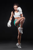Beautiful kickboxer girl dressed in gloves and taking hit b Stock Image