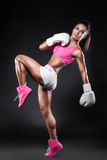 Beautiful kickboxer girl dressed in gloves and taking hit b stock photos