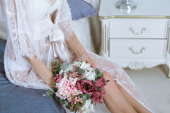 Beautiful sexy lady in elegant white robe and bouquet. Close up female fashion portrait of model indoors. Beauty attractive body of woman in lace lingerie and Royalty Free Stock Photo