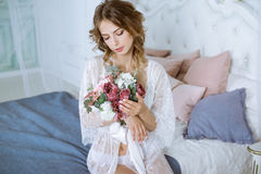 Beautiful sexy lady in elegant white robe. Close up fashion portrait of model indoors. Beauty brunette woman and bouquet. Attractive female body in lace Stock Photo