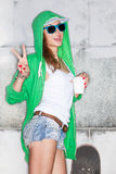 Beautiful sexy lady in jeans shorts with skateboard against  gre Royalty Free Stock Images
