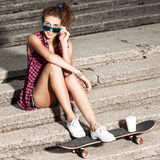 Beautiful sexy lady in jeans shorts with skateboard at stone sta Stock Images