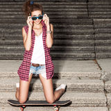 Beautiful sexy lady in jeans shorts with skateboard at stone sta Stock Photography