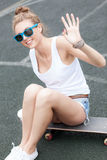 Beautiful sexy lady in jeans shorts with skateboard and to-go cu Royalty Free Stock Images