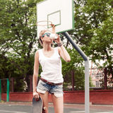 Beautiful sexy lady in jeans shorts with skateboard and to-go cu Royalty Free Stock Photography