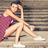 Beautiful sexy lady in jeans shorts with skateboard and to-go cu Royalty Free Stock Photo