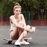 Beautiful sexy lady in jeans shorts with skateboard and to-go cu Stock Images