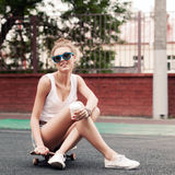 Beautiful sexy lady in jeans shorts with skateboard and to-go cu Stock Photo