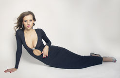 Beautiful sexy lady laying in studio in amazing dress isolated Stock Images