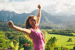 Beautiful sexy lady standing on the top of the peak. With an amazing view on Kauai island in Hawaii watching landscape, mountains and green nature Royalty Free Stock Photos