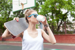 Beautiful sexy lady in white t-shirt with skateboard and to-go c Stock Photo