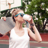 Beautiful sexy lady in white t-shirt with skateboard and to-go c Royalty Free Stock Photography