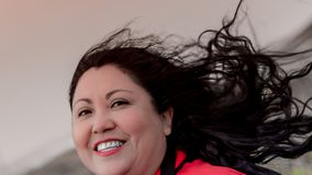 Beautiful sexy latin mexican woman with long black hair tousled by the wind. Happy and smiling enjoying a wonderful day in the Netherlands royalty free stock photo