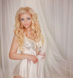 Beautiful sexy long-haired blonde woman sitting on a bed Stock Image
