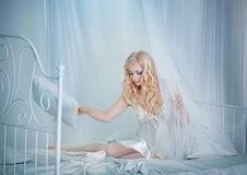 Beautiful sexy long-haired blonde woman sitting on a bed Stock Photos