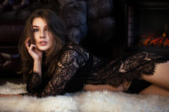 Beautiful sexy long-haired woman in black lingerie posing in the interior. The beauty of the face and body. Royalty Free Stock Photos