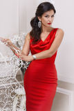 Beautiful sexy luxurious well-groomed young woman in a red slinky dress earrings with diamonds and watches long black hair standin Stock Photos