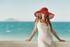 Beautiful model in red hat with red lips looking at camera stock image