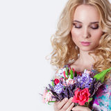 Beautiful sexy modest sweet tender girl with curly blond hair standing on white background with a bouquet of flowers of lavender Royalty Free Stock Image