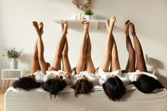 Beautiful sexy multiethnic girls lying on bed raise legs up
