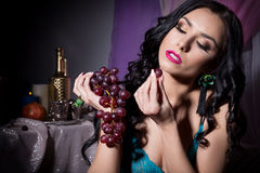 Beautiful sexy oriental woman in black lace lingerie with long hair eating grapes in the dark room Royalty Free Stock Photography