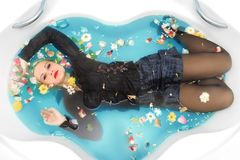 Beautiful passionate attractive girl with blonde wet hair, bright makeup and wet black blouse and mini skirt lying in bathtub. With blue water and bright stock photos