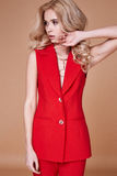 Beautiful sexy pretty girl wear red silk suit jacket and pants s. Kinny body shape lady boss business woman skin tan long blond hair party style fashion cloches Stock Photo