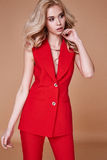 Beautiful sexy pretty girl wear red silk suit jacket and pants s. Kinny body shape lady boss business woman skin tan long blond hair party style fashion cloches Royalty Free Stock Images