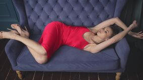 Beautiful sexy pretty lady lie on the sofa woman wear gentle red silk dress clothes style for date party fashion model glamour lux