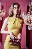 Beautiful sexy pretty woman wear yellow color dress casual style. Clothes party long blond hair makeup cosmetic fashion model pose accessory hand bag interior Stock Images