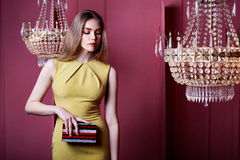Beautiful sexy pretty woman wear yellow color dress casual style. Clothes party long blond hair makeup cosmetic fashion model pose accessory hand bag interior Stock Image