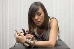 Beautiful sexy professional tattoo master with machines in hand Stock Images