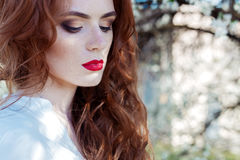 Beautiful sexy red-haired girl with freckles with red lipstick on her lips near blooming trees in the city on a sunny clear day Stock Photos