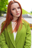 Beautiful sexy red-haired girl in a green coat walking in the park. Beautiful sexy red-haired girl  in a green coat walking in the park Royalty Free Stock Image