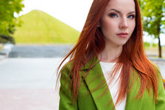 Beautiful sexy red-haired girl in a green coat walking in the park. Beautiful sexy red-haired girl  in a green coat walking in the park Royalty Free Stock Photos