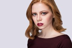 Beautiful sexy redhead girl. With fresh, bright makeup grey big eyes in purple sweater on a white background isolate hands in hair looking into the camera lips Stock Photo