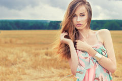 Beautiful romantic girl with red hair wearing a colored dress, the wind standing in the field on a cloudy summer day stock photo