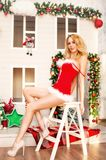 Beautiful sexy santa claus girl with long legs in red dress Stock Images