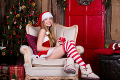 Beautiful, sexy Santa female having fun and smiling near the Christmas tree, sitting in vintage chair. New year Stock Photo