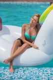 Beautiful sexy slender blonde sitting big inflatable unicorn pool Royalty Free Stock Image