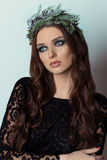 Beautiful sexy slim elegant woman with bright makeup Smoky Eyes in the New Year wreath of Christmas tree and cones Royalty Free Stock Images