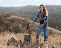 Beautiful sexy smiling woman chopping wood with axe Stock Image
